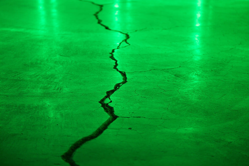 Crack in cement with green light