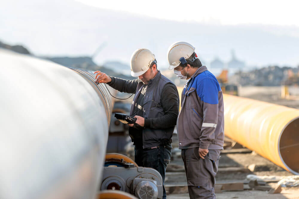 Two NDT Technicians looking at a pipeline